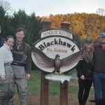 A group of people standing next to the Blackhawk Fly Fishing sign